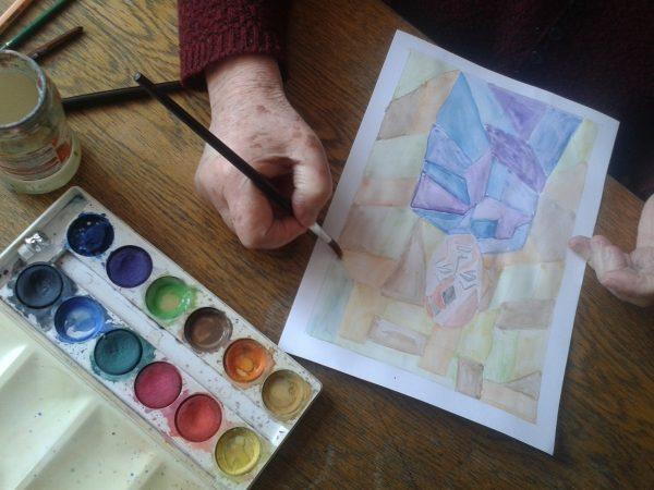 Dłoń seniora, w dłoni pędzel nad kartką z namalowaną akwarelą, obok otwarta paleta farb