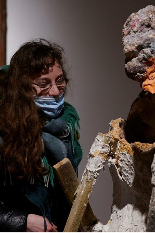 Kobieta ogląda rzeźbę na wystawie autorstwa Łukasza Zbroi.
