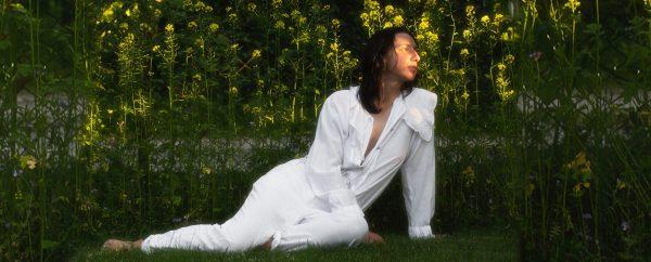 Na zdjęciu Antonina Nowacka. Zdjęcie osoba w białym ubiorze siedzi na trawie w tle zieleń drzew i krzewów.